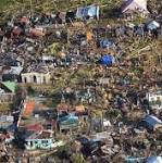 Typhoon survivors swarm airport in city littered with bodies