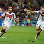Mario Gotze of Germany celebrates scoring the winning goal with Thomas Muller